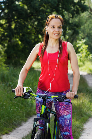 woman on phone: Young attractive woman in the sportswear with a sport bicycle and a phone, soft focus background