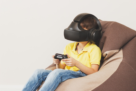 Boy plays game with virtual reality glasses indoors. Digital vr device