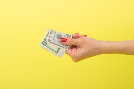 American dollars in the womans hand, on the yellow background Stock Photo