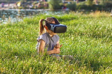 sensation: Little beautiful girl plays game with virtual reality glasses outdoors. Digital vr device Stock Photo