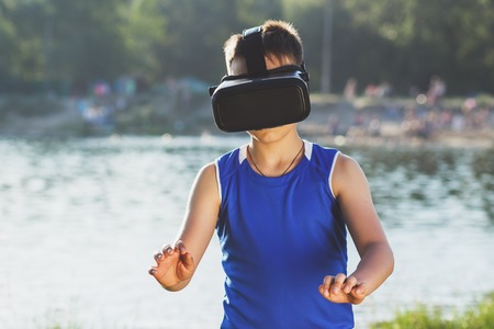 sensation: The boy plays game with virtual reality glasses outdoors. Digital vr device Stock Photo