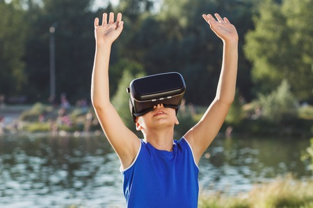 The boy plays game with virtual reality glasses outdoors. Digital vr device Stock Photo