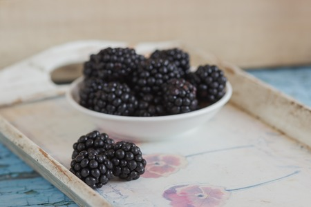Blackberry in the white bowl on the wooden tray, soft focus background