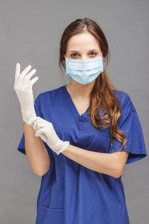 Vrouw arts in de blauwe medische uniform, met steriele handschoenen op de handen en een masker op het gezicht, grijze achtergrond