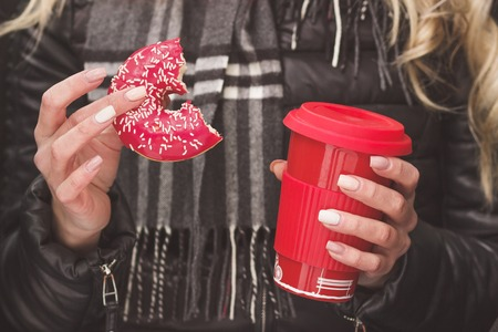 woman's hands: Cup of hot drink and red donut in the womans hands, soft focus background