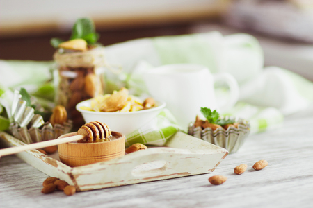 Honey in the bowl, muesli, mint leaves, almonds and jar with milk on the wooden tray, soft focus background