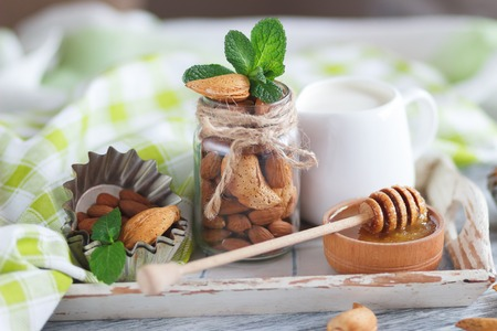 Honey in the wooden bowl, mint leaves, almonds and jar with milk on the wooden tray, soft focus background