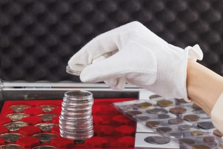 Hand in the glove holds gold collector coin, soft focus background Imagens
