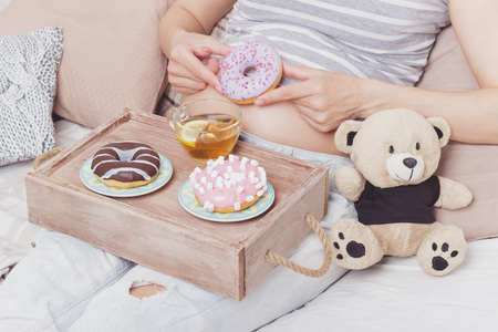 Pregnant woman with different colored donuts and a cup of tea, soft focus background