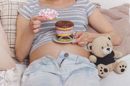 Pregnant woman with different donuts on the plate, soft focus background 스톡 콘텐츠