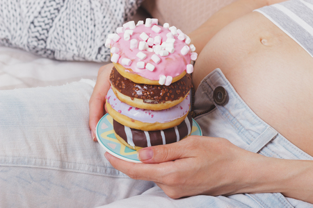 Pregnant woman with different donuts on the plate, soft focus background Stock Photo