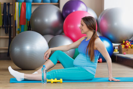 Pregnant woman sits on the mat in the gym with a bottle of water in the hand, blurred background