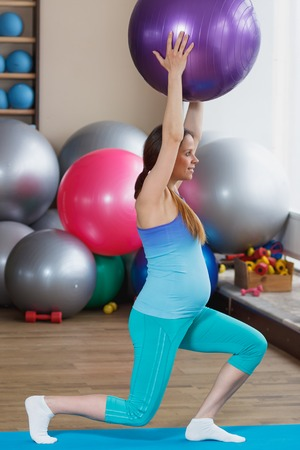 Pregnant woman with a fitness ball in the hands, soft focus background