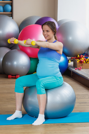 Pregnant woman sits on the fitness ball in the gym, soft focus background