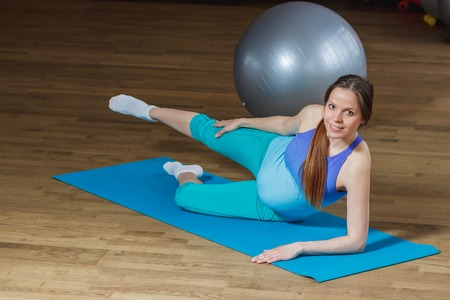 Pregnant woman makes exercise on the mat, soft focus background