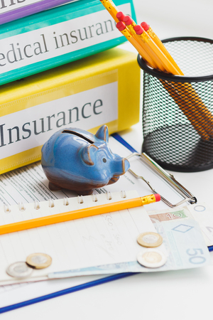 Clean insurance form, magnifying glass and money, blurred background