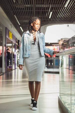 Young dark-skinned woman dressed in casual clothes in the mall, blurred background Stock Photo