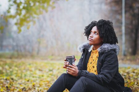 Dark-skinned woman dressed in casual clothes holding cup of hot drink, enjoying coffee or tea, soft focus background