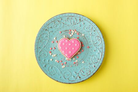 Pink cookie heart shaped with different patterns on the light yellow background