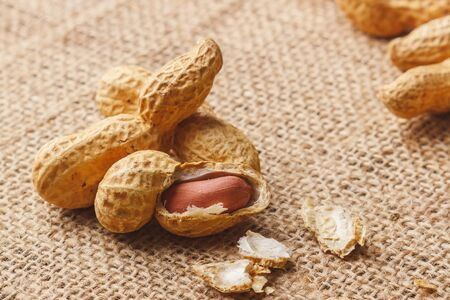 Background from golden peanuts in the shells, soft focus background