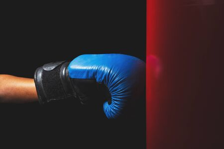 Body part: woman hand with the blue boxing gloves, dark background