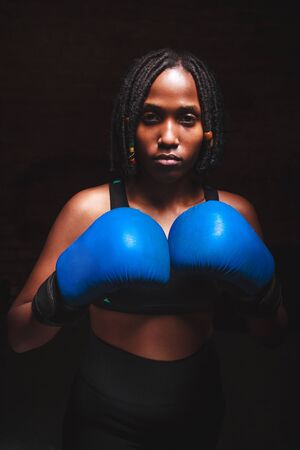 beautiful woman with the blue boxing gloves,black background