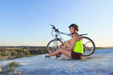 Young sporty woman with a bike on a sunset, soft focus background