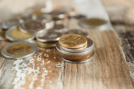 Gold, silver coins and decorative house, wooden background