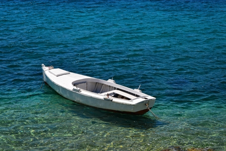 azure: Tiny wooden boat on an azure sea