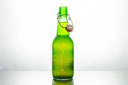 lighted: Isolated green bottle of Grolsch beer on a white background lighted from behind Stock Photo