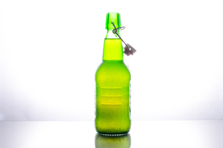 lighted: Isolated green bottle of beer on a white background lighted from behind