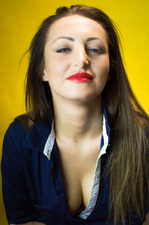 cleavage: Beautiful young woman wearing dark blue shirt with long hair, red lips and deep cleavage on a yellow background Stock Photo
