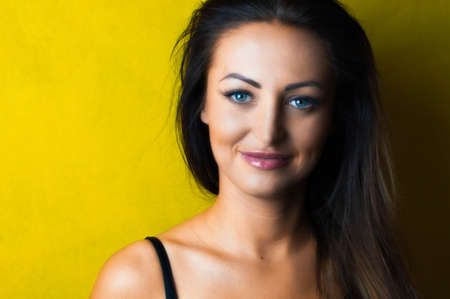 cleavage: Beautiful young woman wearing black shirt with long hair, red lips and deep cleavage on a yellow background