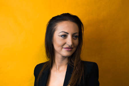 cleavage: Beautiful young business woman wearing a black shirt and jacket with long hair, red lips and deep cleavage on a yellow background Stock Photo