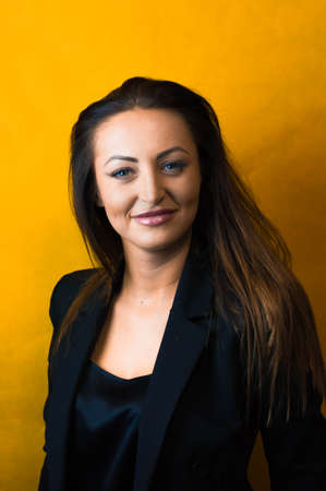 beautiful cleavage: Beautiful young business woman wearing a black shirt and jacket with long hair, red lips and deep cleavage on a yellow background Stock Photo