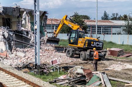 JCB excavator demolishes old building. Editorial