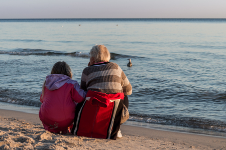 Grandmother and granddaughter crouching on a sea shore during sunrise.