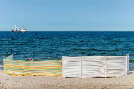 baffle: White and colorful striped windbreaks at the beach