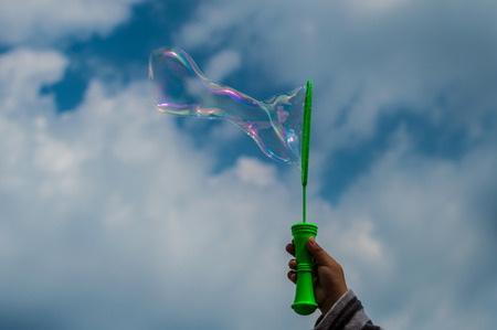Baby doing soap bubbles - hand on sky, clouds background.