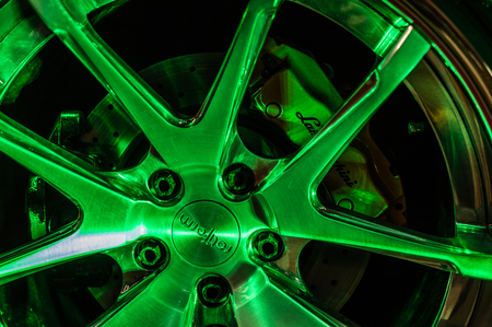 Close up of a cars rim, wheel and breaks with Lamborghini emblem. Selective focus and green light. Editorial
