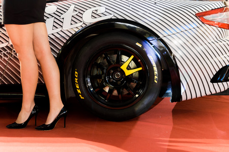 Pirelli logo close up with the girl next to the car.
