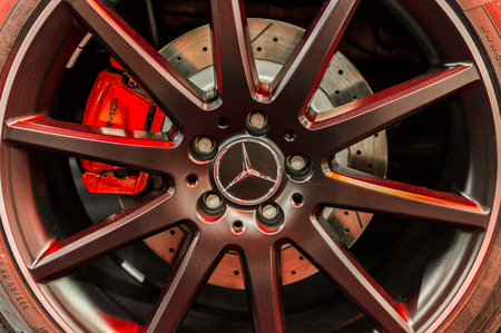 Close up of a cars rim, wheel and breaks with Mercedes Benz emblem.