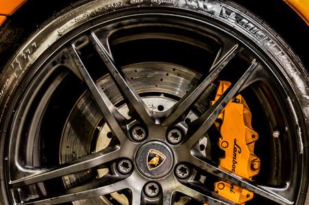 Close up of a cars rim, wheel and breaks with Lamborghini emblem.
