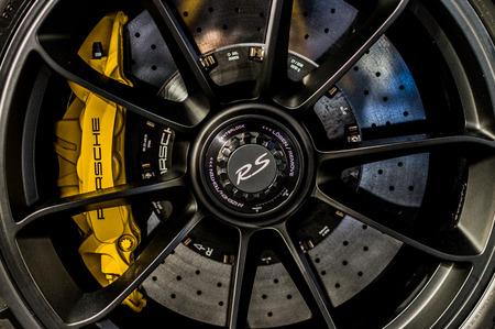 Close up of a car's rim, wheel with Porsche emblem.