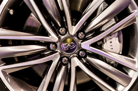 daimler: Close up of a cars rim, wheel with Infinity emblem.