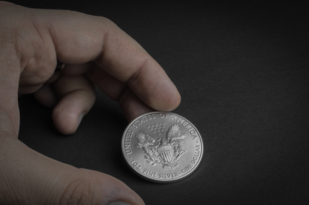 Silver one dollar coin standing on black surface - business concept, isolated.