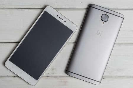 Smartphones on wooden background - Oneplus 3t gunmetal Stock Photo