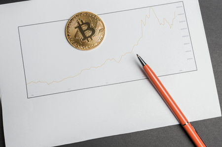 Bit coin laying on a table with exchange rate chart over time and a pen