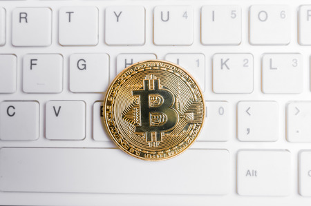 Bitcoin laying on a white computer keyboard Stok Fotoğraf