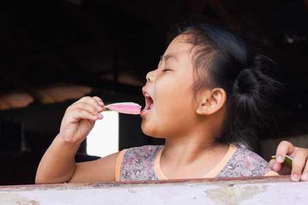 deliciously: Lovely Asian girl kid eat deliciously sweet candy beside the window